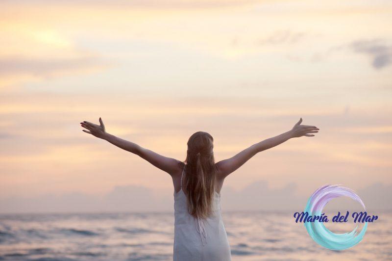 Mujer expande sus brazos soltando la razón frente al mar